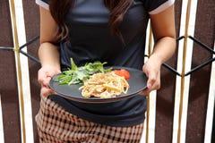 Die Spaghettis Carbonara mit grünen Gemüse- und roten Tomaten schnitten in Stücke in den Händen stockfotografie