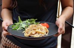 Die Spaghettis Carbonara mit grünen Gemüse- und roten Tomaten schnitten in Stücke in den Händen stockbild