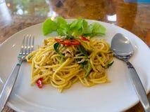 Die Spaghettis, grüner Curry mit Schweinefleisch auf einer weißen Platte Auf dem Holztisch Stockfotografie