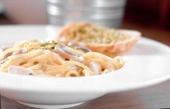 Die Spaghettiteigwaren mit Wurst und Knoblauch-Brot in der weißen Platte Stockfoto