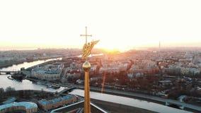 Die Spanne des Engels auf dem Kirchturm im Peter und in Paul Fortress bei Sonnenuntergang - Luftschießen der historischen Mitte stock footage
