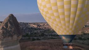 Die Spanne eines gro?en gelben Ballons, in einem Korb von Leuten, Nahaufnahme Fliegen ?ber den Bergen - Panorama von Cappadocia stock footage