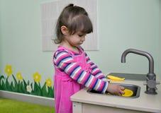 Die Spiele des kleinen Mädchens in der Küche der Kinder Stockbilder
