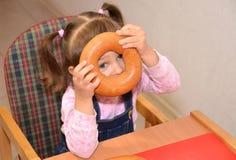 Die Spiele des kleinen Mädchens ungefähr während des Lebensmittels Stockfotografie