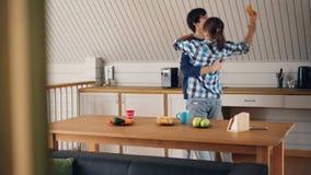 Die spielerischen jungen Leute haben Spaß in der Küche Gebäck essend und Musik zu Hause hören während des Frühstücks tanzend stock footage