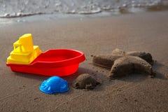 Die Spielwaren der Kinder für Sand und Starfish machten vom Sand Sandy-Strand, sonniger Tag lizenzfreies stockbild