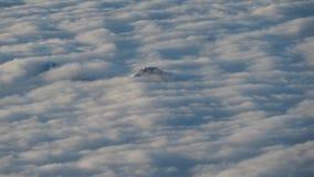 Die Spitzen der Berge steigen heraus von den Wolken, die die Erde bedecken Landschaft vom Flugzeugfenster Stockfotos