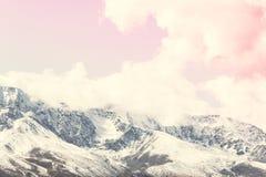 Die Spitzen des schneebedeckten Gebirgszugs unter dem rosa Himmel stockbilder