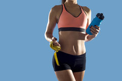 Die Sportfrau, die Wasserflasche halten und das Maß nehmen das Zeigen der dünnen perfekten ABS und des Magens auf Stockbild