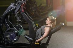 Die sportive Frau, die Gewichte verwendet, bedrängen Maschine für Beine Gymnastik stockfotografie