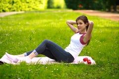 Die sportive junge Frau, die Eignung tut, trainiert im grünen Park stockbild