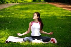 Die sportive junge Frau, die im Sonnenschein, Yoga tuend sich entspannt, trainiert Stockbilder