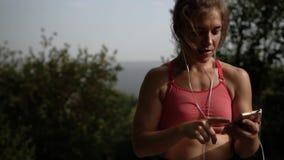 Die Sportlerin, die Kopfhörer trägt und schaltet Musik ein stock video footage