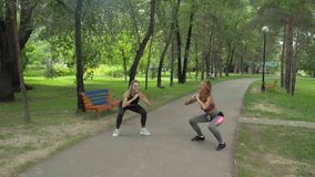 Die Sportlerinnen, welche die Sportkleidung tut Hocken tragen, trainieren draußen Eignungs-weibliches Ausarbeiten im Park stock footage