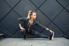 Die sportliche junge Eignungsfrau, die Sport tut, trainiert bei auf schwarzem Hintergrund draußen stehen, weiblich im Trainingsga lizenzfreie stockbilder