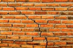 Die Sprungswand vom Ziegelstein und vom Ziegelsteinhintergrund, roter Sprungsziegelstein und Muster des Sprungsbacksteinmauerhint Stockfotografie