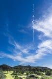 Die Spur von Düsenflugzeugn im Himmel über einer ländlichen Landschaft Lizenzfreie Stockfotos