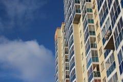 Die städtische mehrstöckige moderne Wohnhochhausneubaufassade bequem mit Windows gegen den blauen Himmel oben stockfoto