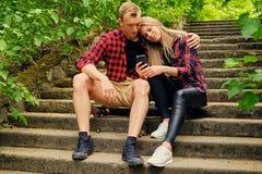 Die städtischen Paare, die auf den Schritten in der Wildnis sich entspannen, parken Stockfoto