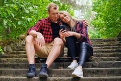 Die städtischen Paare, die auf den Schritten in der Wildnis sich entspannen, parken Lizenzfreie Stockfotografie
