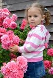 Die Stände des kleinen Mädchens nahe einem Busch des Blühens stiegen Lizenzfreie Stockfotos
