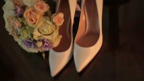 Die Stöckelschuhe der Luxusfrauen des weißen Leders auf dem Tisch nahe bei dem ausgezeichneten bunten Hochzeitsblumenstrauß von stock video