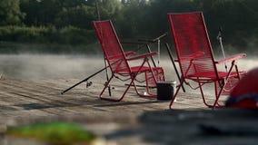 Die Stühle, die am Fischenpier auf Hintergrundmorgen stehen, nebeln über Flusswasser ein stock video