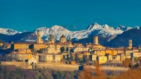 Die Stadt von Bergamo mit Hoch hinter den weißen Bergen des Schnees Stockbilder