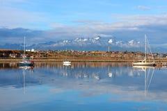 Die Stadt von Ushuaia, die Boote und die Berge im Hintergrund werden im Wasser reflektiert Stockfotografie