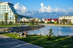 Die Stadtskyline, die den Boden, den Teich und die Berge auf dem Horizont übersehen Lizenzfreies Stockbild