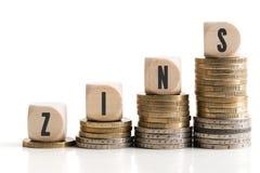 Die Staplungsmünzen, die symbolisieren, Zinssätze mit dem Wort ` anhebend, interessieren ` auf Deutsch Lizenzfreies Stockbild
