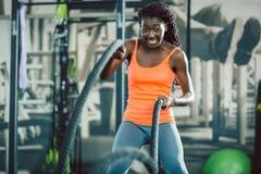 Die starke Frau, die mit Kampf trainiert, ropes während des Funktionstrainings lizenzfreie stockbilder