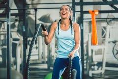 Die starke Frau, die mit Kampf trainiert, ropes während des Funktionstrainings stockfotografie