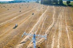 Die Starkstromleitungen auf der Weizenstoppel Lizenzfreie Stockfotos