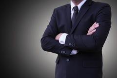 Die stehenden gekreuzten Arme der Geschäftspersönlichkeit tragen einen Anzug auf einem grauen Hintergrund oder einem Hintergrund Lizenzfreie Stockfotografie