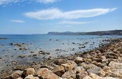 Die steinige Küstenlinie gegen das Meer und den Himmel Lizenzfreies Stockbild