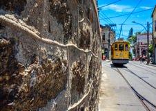 Die Steinwand, der blaue Himmel und die altmodische gelbe Tram in Sankt Lizenzfreies Stockfoto