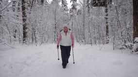 Die stilvoll gekleidete ältere Frau nimmt an einem neuen Typ Sport gehend in schneebedecktes Holz des Winters teil Aktiver Pensio stock video