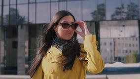 Die stilvolle Frau in einem gelben Regenmantel mit dem langen dunklen Haar gehend hinunter die Straße entfernt ihre Gläser und Sc stock video footage