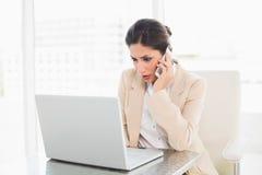 Die Stirn runzelnde Geschäftsfrau, die mit einem Laptop am Telefon arbeitet Lizenzfreie Stockfotos