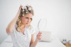 Die Stirn runzelnde herrliche blonde tragende Haarlockenwickleraufstellung Lizenzfreie Stockfotos