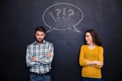 Die Stirn runzelnde Paare, die nach Argument über Tafelhintergrund stehen Stockfoto
