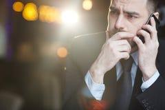 Die Stirn runzelnder Geschäftsmann Talking durch Smartphone Stockfotos