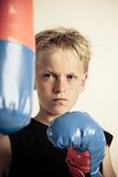 Die Stirn runzelnder Junge, der schwarzes Hemd und Boxhandschuhe trägt Lizenzfreies Stockfoto