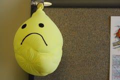 Die Stirn runzelnder trauriger Gesichtssmileygesichts-Gelbballon entlüftet Stockfotografie