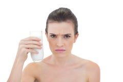 Die Stirn runzelndes natürliches braunes behaartes Modell, das ein Glas Milch hält Lizenzfreie Stockbilder