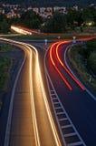 Die Straße am Abend mit Licht streift Scheinwerfer Stockbild