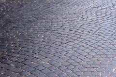 Die Straße, abgedeckt mit schwarzen Steinen Lizenzfreie Stockbilder