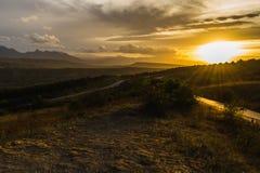 Die Straße in den Bergen bei Sonnenuntergang Stockfotos