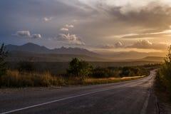 Die Straße in den Bergen Wolken im Sonnenuntergang Stockfoto